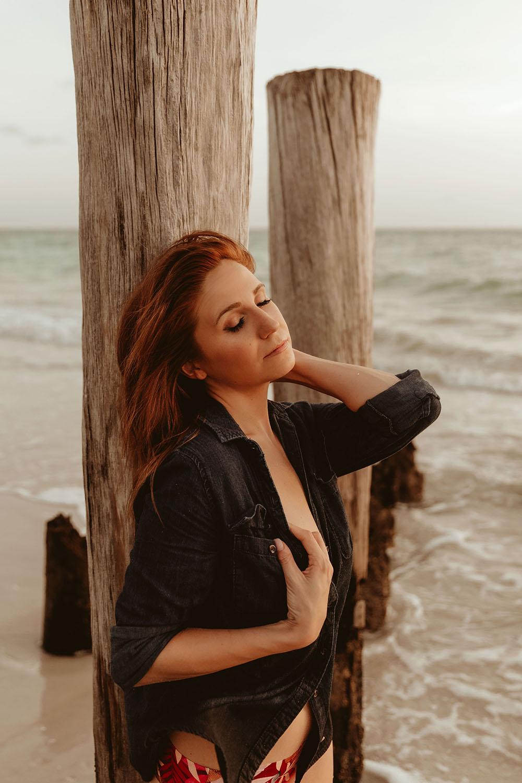 Naples Boudoir Photographer, woman posing against a pillar at the beach