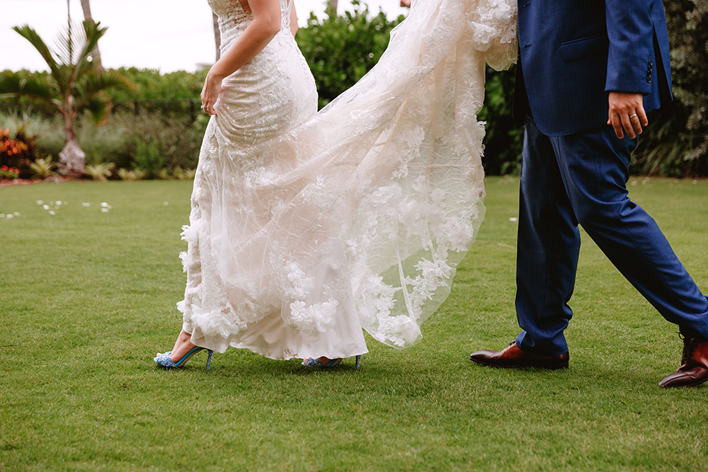 Naples Wedding Photographer, groom holding brides dress while walking on the grass