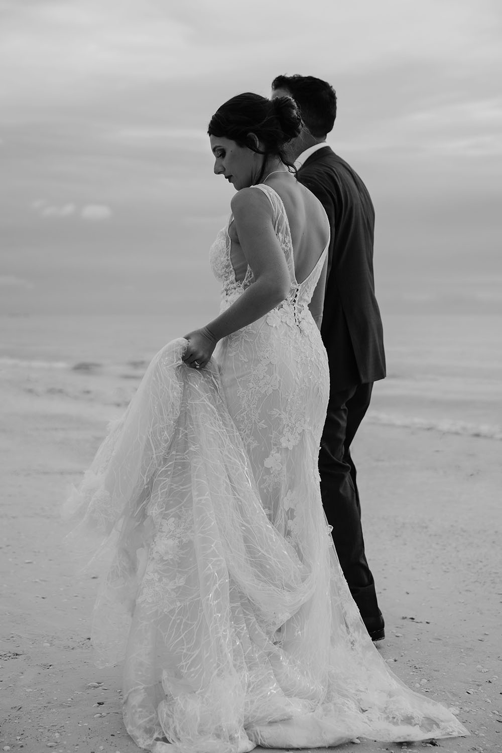 Naples Wedding Photographer, black and white of bride and groom walking on the beach