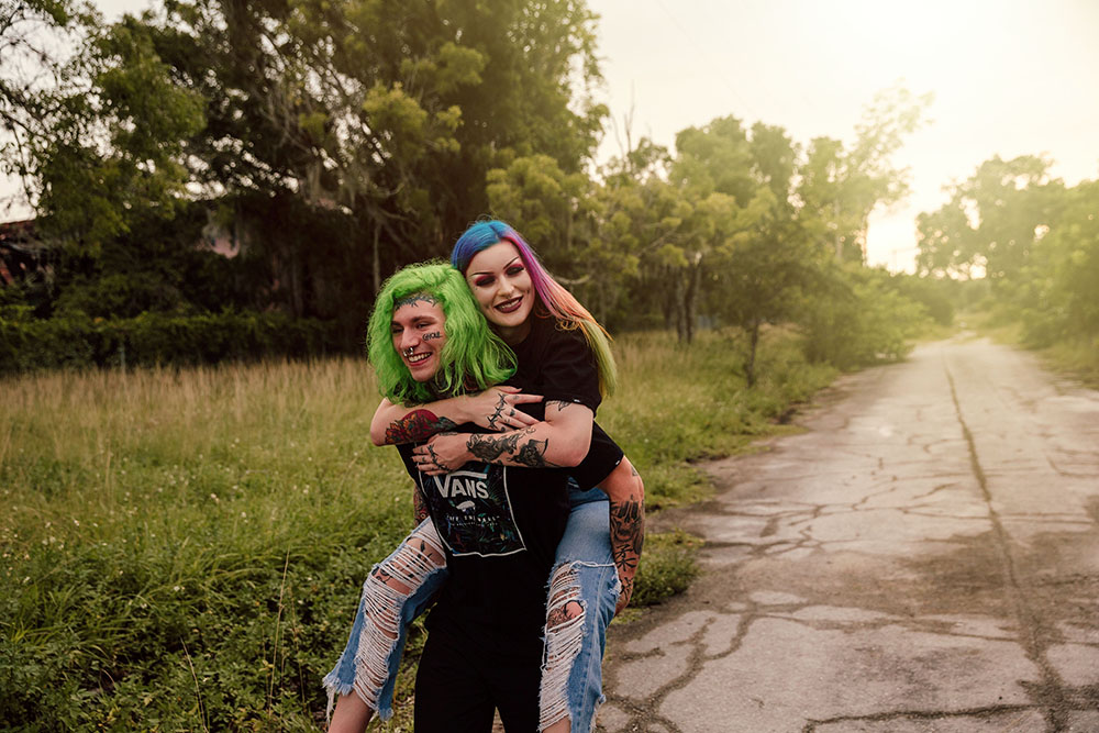 Naples Couples Photographer, man with green hair giving a piggy back ride to woman