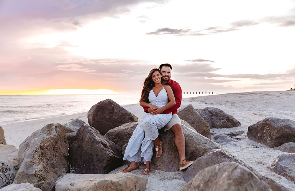 Naples Couples Photographer, couple sitting on rocks at the beach
