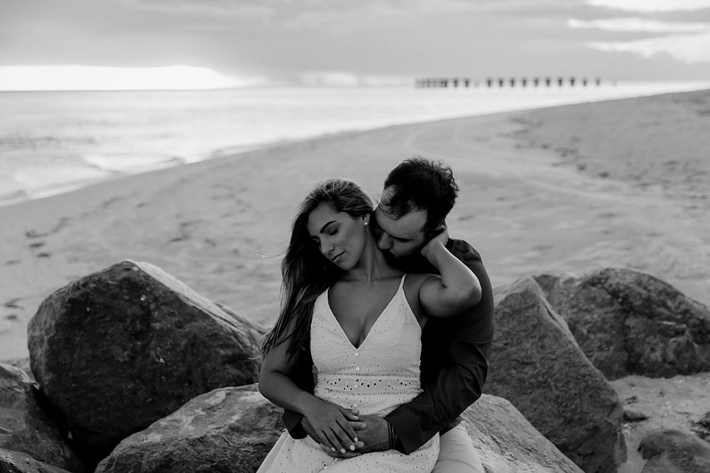Naples Couples Photographer, black and white of couple sitting on rocks at the beach