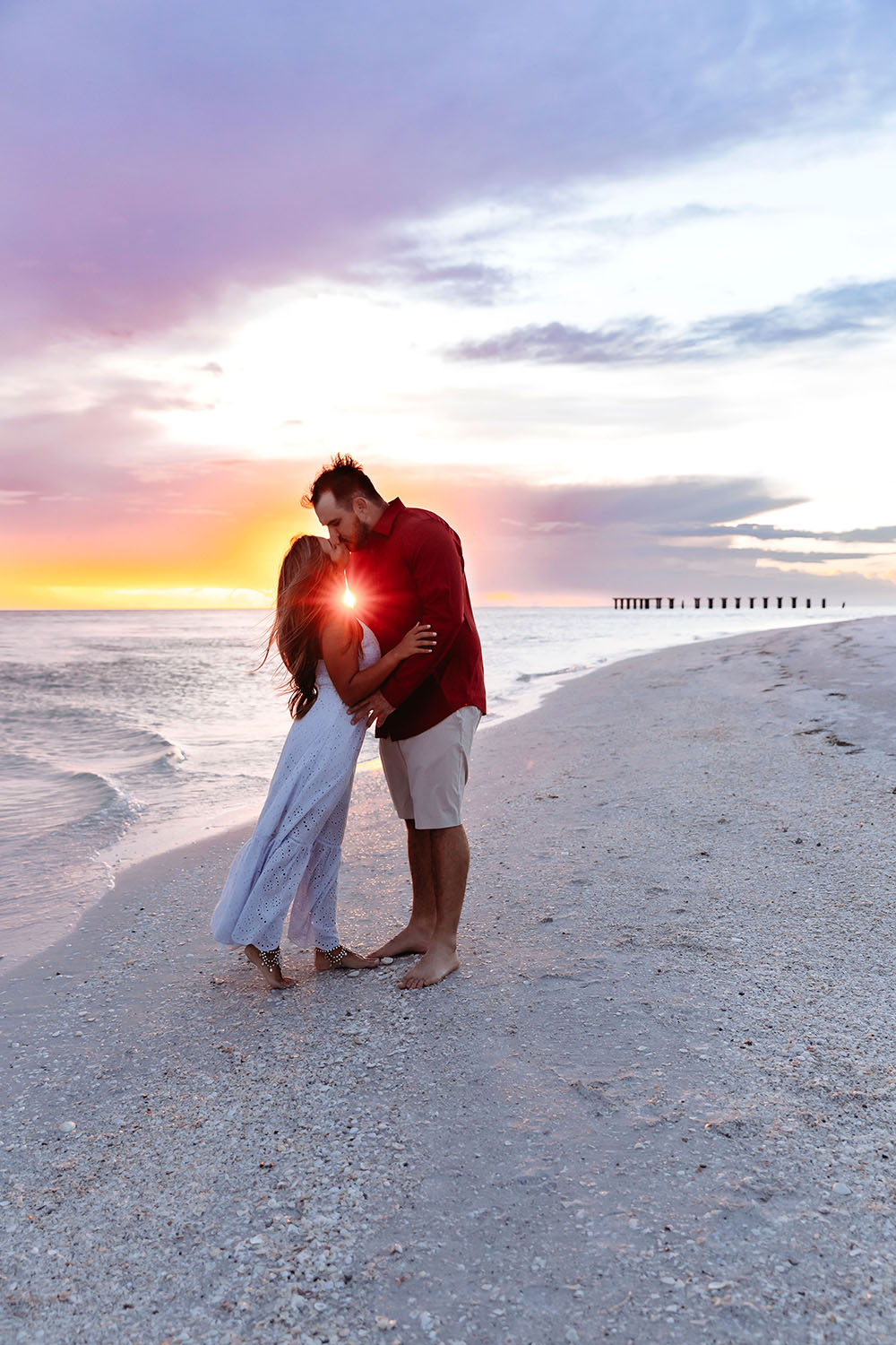 Naples Couples Photographer, couple kissing on the beach with sunset behind them
