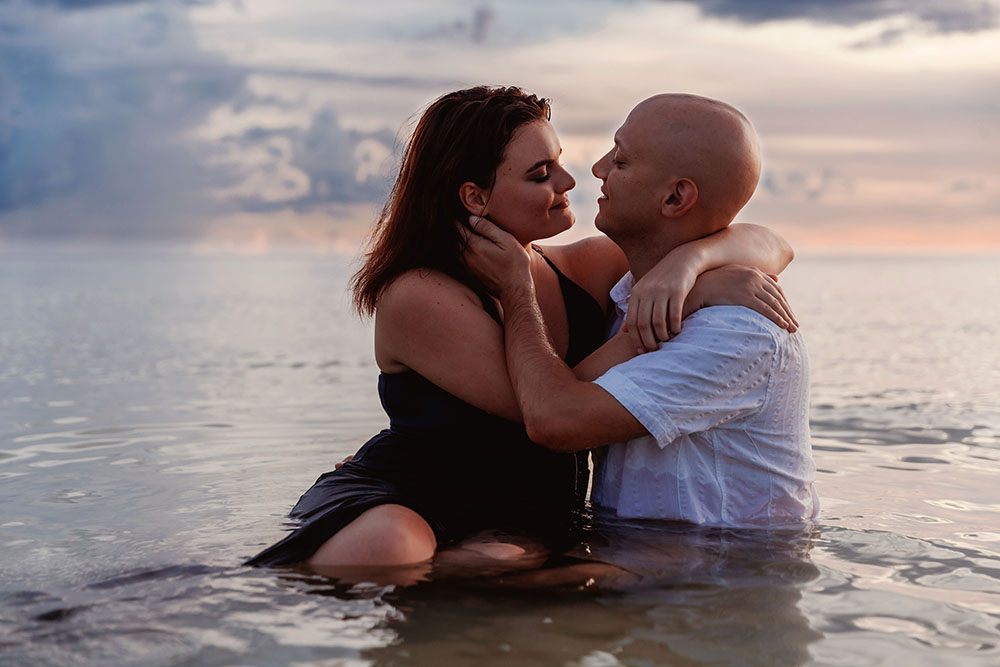 Naples Couples Photographer, couple sitting in the ocean looking at each other