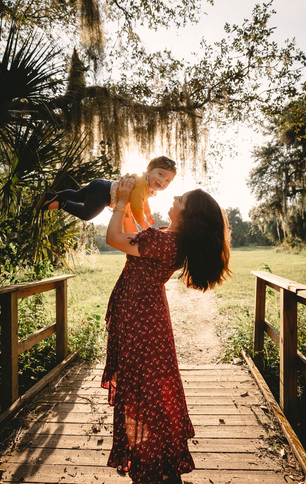 Naples Family Photographer, mother lifting baby girl into the air