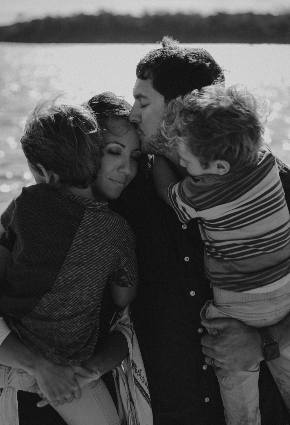 Naples Family Photographer, family of 4 huddled together near the water