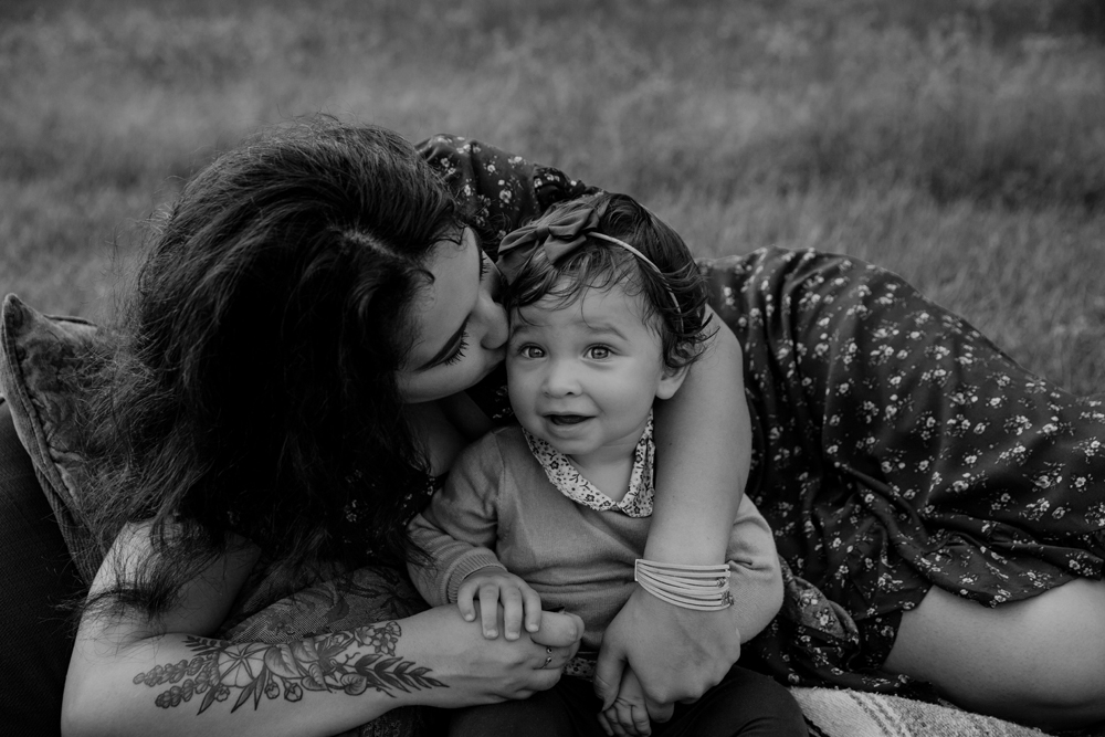 Naples Family Photographer, mother laying down and kissing baby girl on the cheek