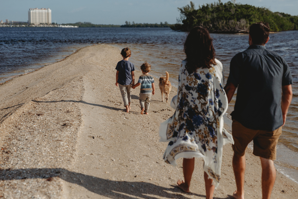 Naples Family Photographer, family walking on beach with dog