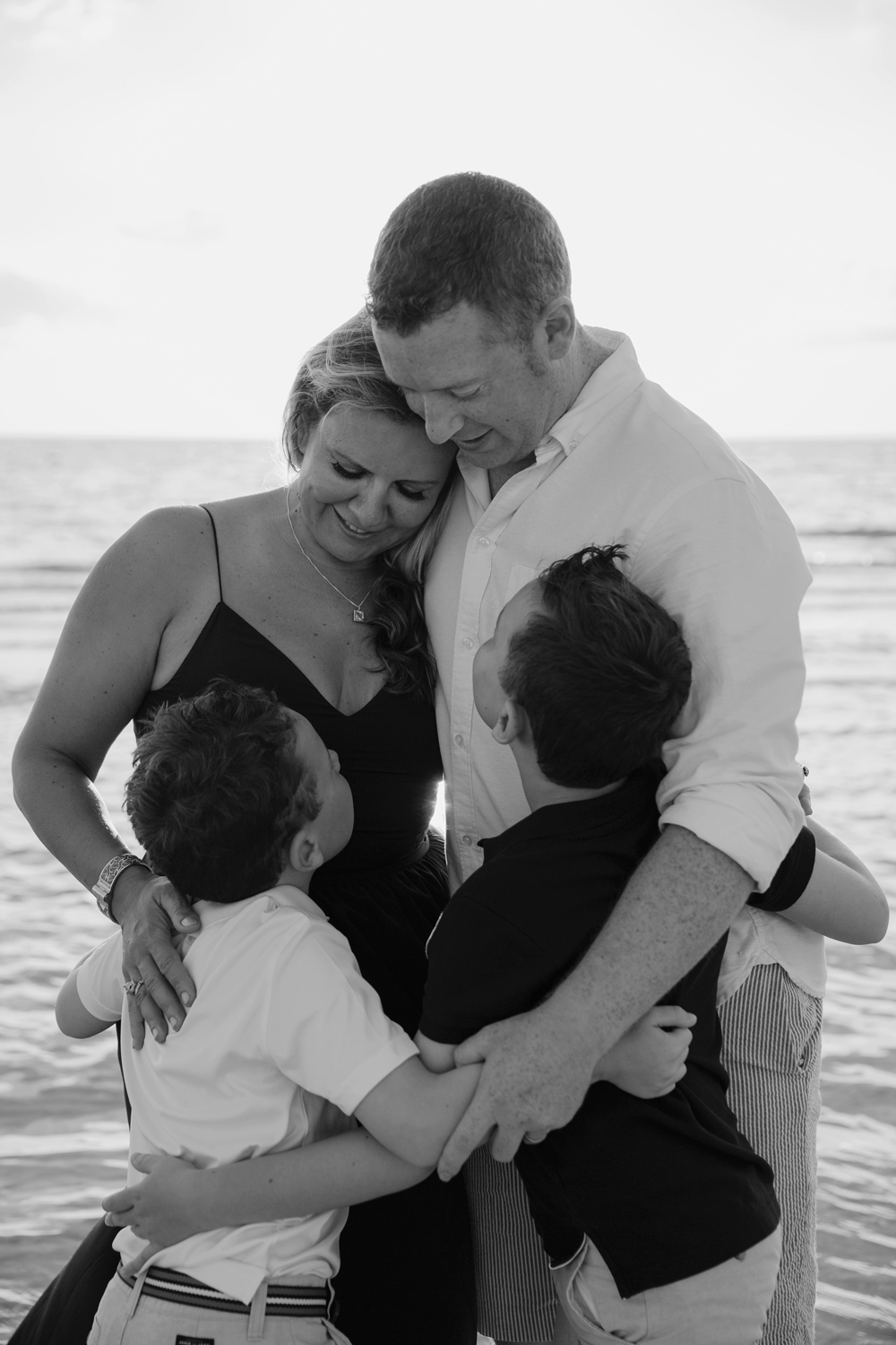 Naples Family Photographer, family of four standing next to ocean