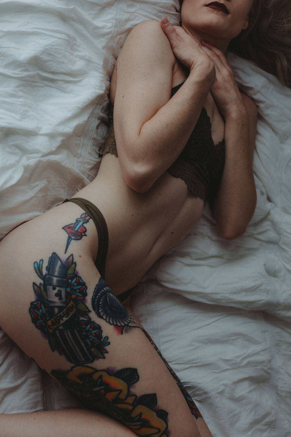 Naples Boudoir Photographer, tattooed woman laying on bed with her hands resting on her chest