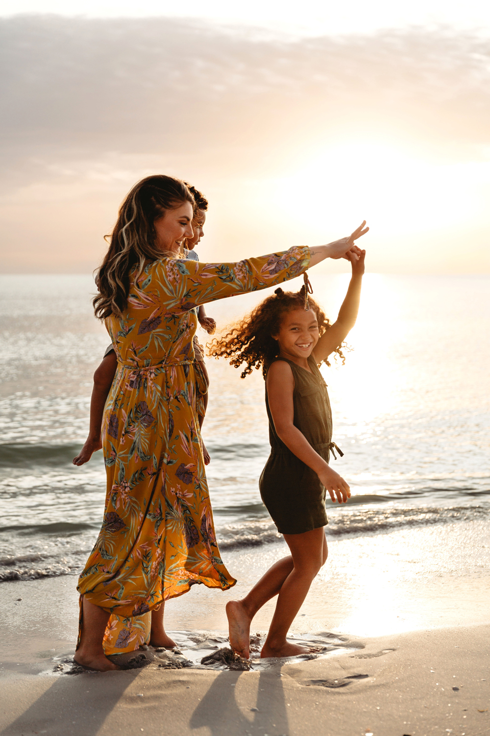 Naples Family Photographer, mother twirling daughter around