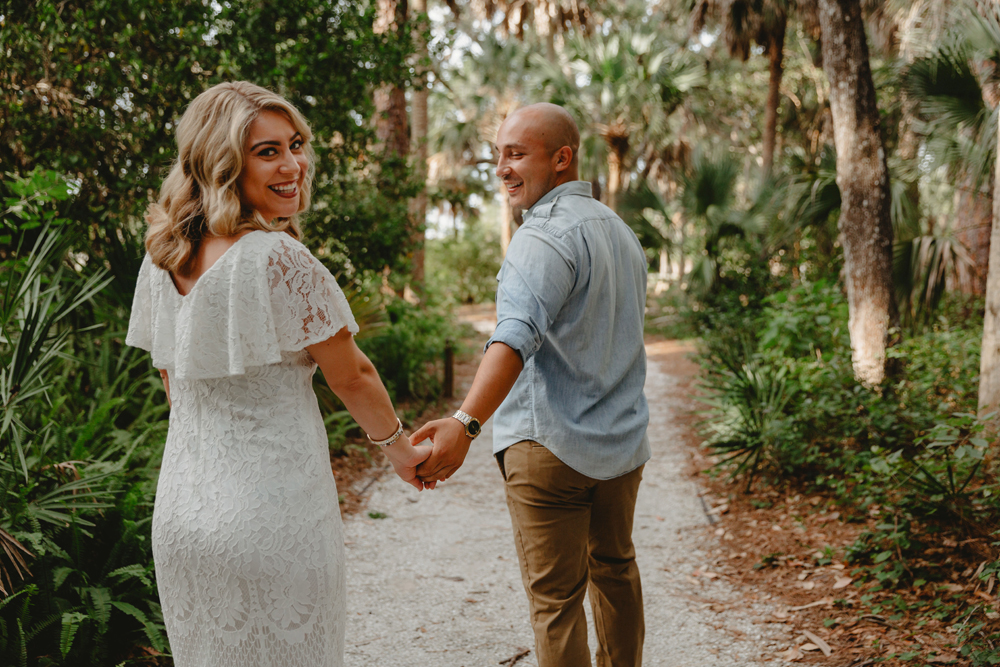 Naples Couples Photographer, couple smiling and laughing as they walk down a pathway