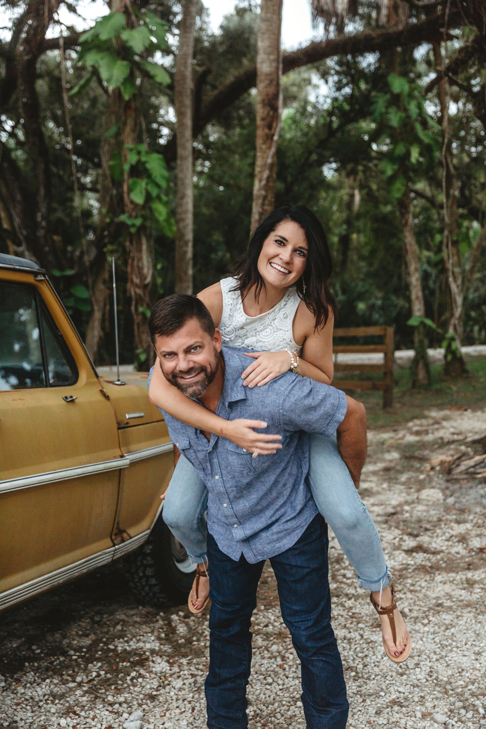 Naples Couples Photographer, couple smiling and laughing as they piggyback ride