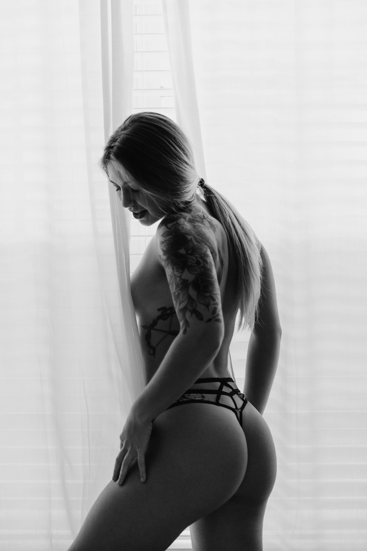 Naples Boudoir Photographer, woman behind window curtains