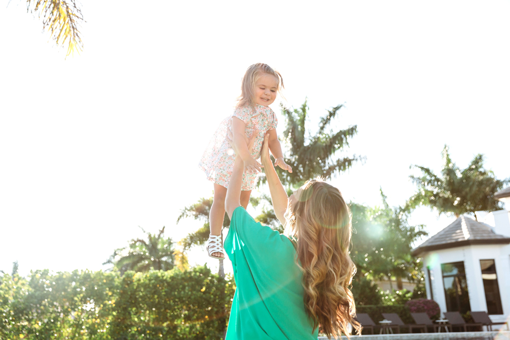 Naples Family Photographer, mother tossing little girl in the air