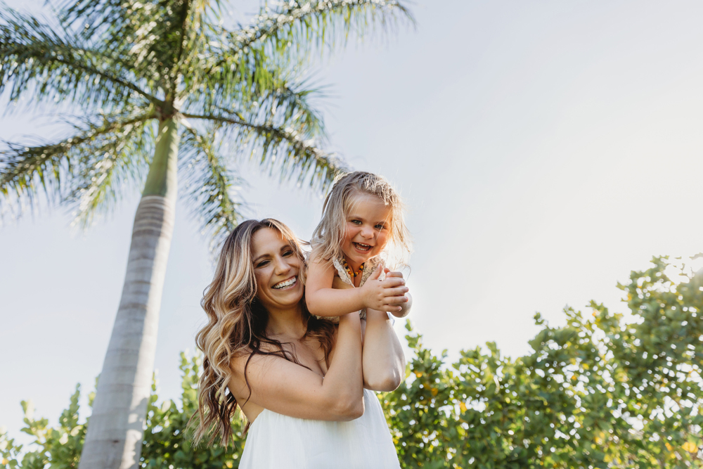 Naples Family Photographer, mother holding daughter on her shoulder