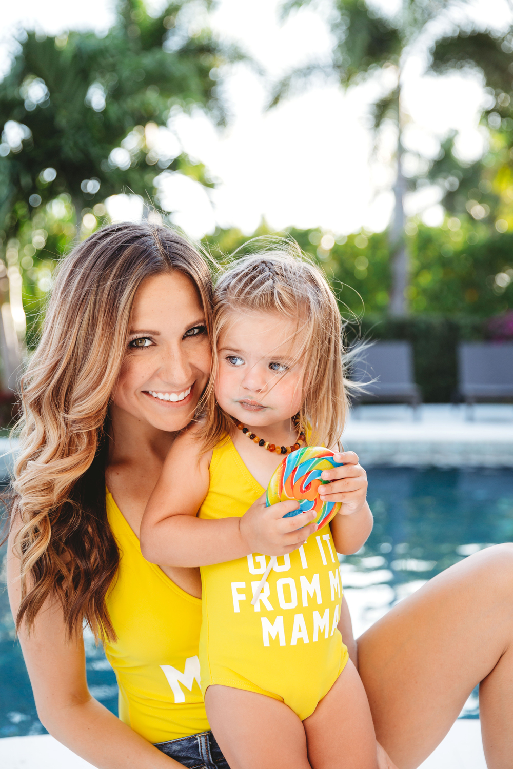 Naples Family Photographer, mother holding up daughter with matching bathing suit