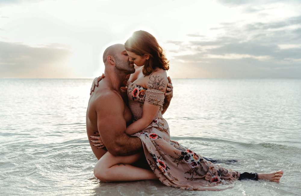 Naples Couples Photographer, couple kneeling in the ocean kissing each other