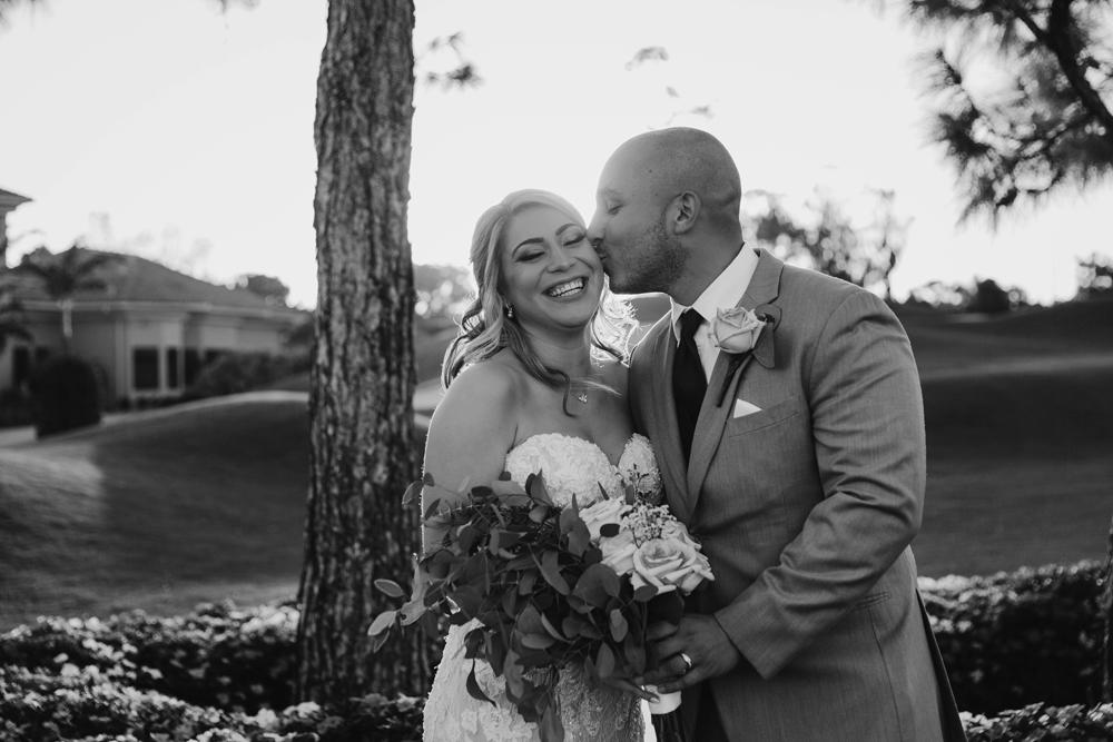 Naples Wedding Photographer, groom kissing bride on her cheek