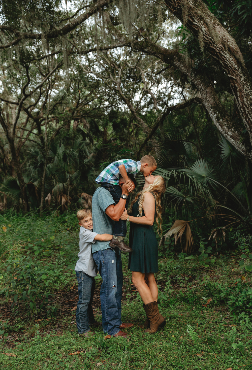 Naples Family Photographer, little boy leaning off of dad's shoulders to give mama a kiss