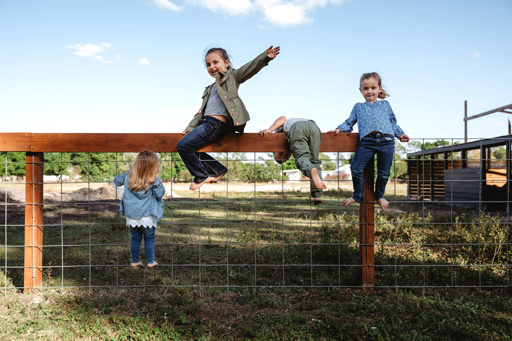 Naples Family Photographer, kids climbing on fence
