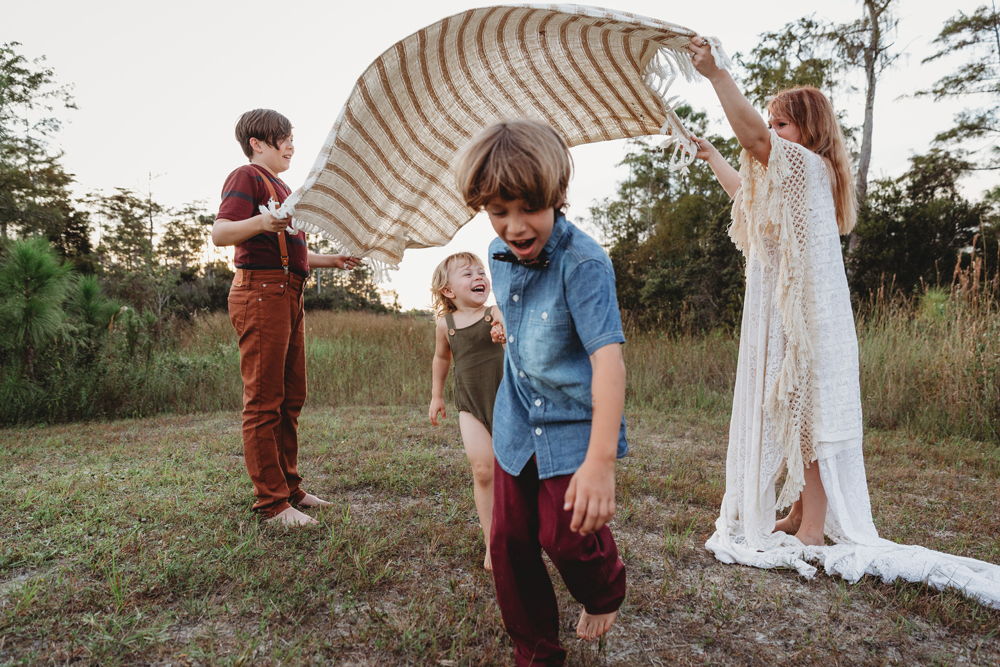Naples Family Photographer, mother and oldest son raising up a blanket over little kids